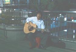 街でギターを弾く米沢