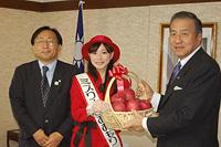 馮代表に県産リンゴを贈るミスりんごの木村さん(中央)と三村知事(左)