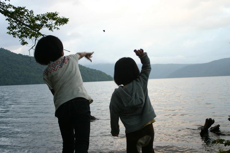 石を投げる二人